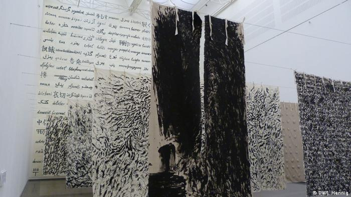 Several huge screens with words and blotches of black paint (Bildergalerie)