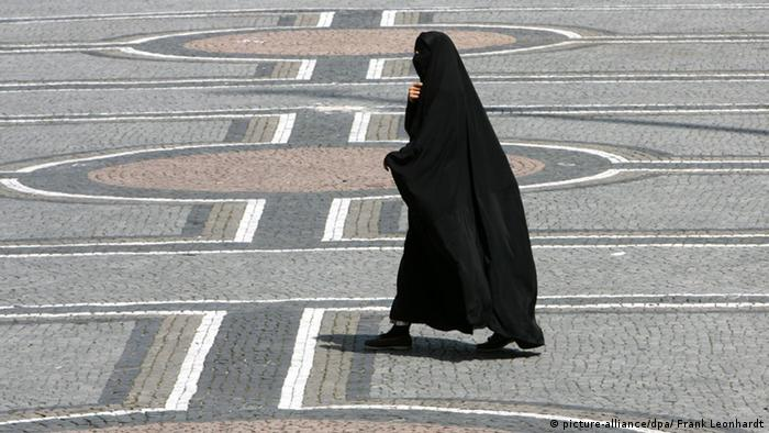 A woman in a burqa walks across a square in Munich