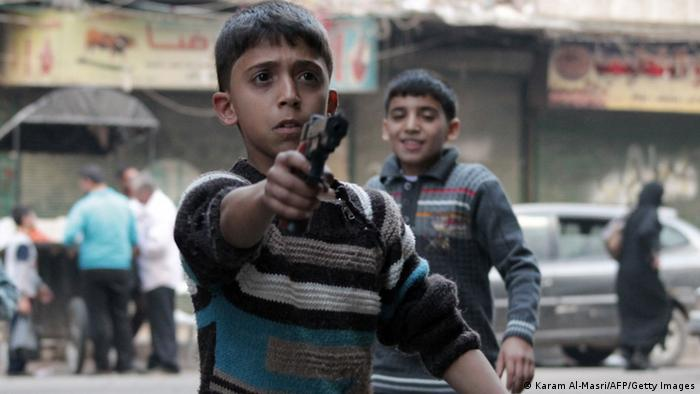 Children play with a gun in Aleppo (Karam Al-Masri/AFP/Getty Images)