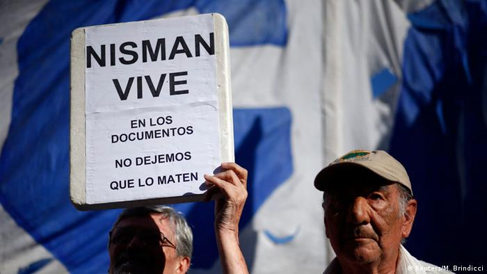 A protester holds up a sign in Buenos Aires, saying that Nisman lives on - through his documents.
