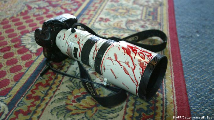 Archive photo from 2003: a wounded photojournalist's camera lies, its white telephoto lens covered in blood, on a rug in a Baghdad hotel.