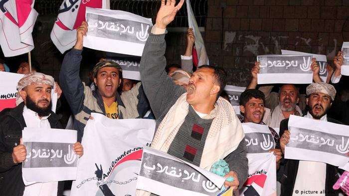 A group of people, including members of Yemen's Revolution Youth Council, hold banners and shout slogans during a demonstration against constitutional declaration issued by the Shiite Houthi movement