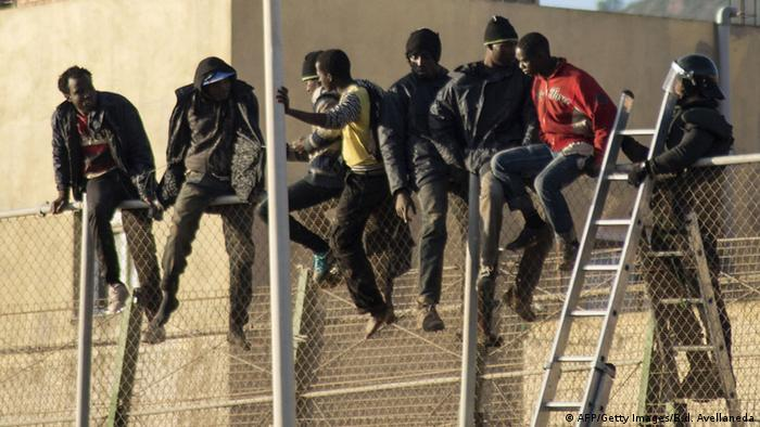 People sitting on a fence in the North African Spanish enclave of Melilla (AFP/Getty Images/B.d. Avellaneda)