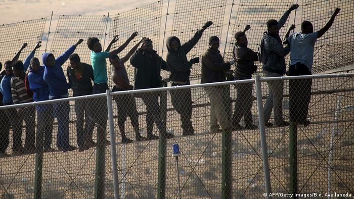 Would-be immigrants stand atop a boarder fence separating Morocco from the north African Spanish enclave of Melilla on May 1, 2014.