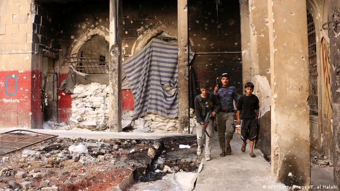 Inmitten eines zerbombten Hauses läuft ein Mann mit zwei Jungen im Arm. Alle Drei haben Maschinengewehre in der Hand. (Foto: Fadi al-Halabi/AFP/Getty Images)