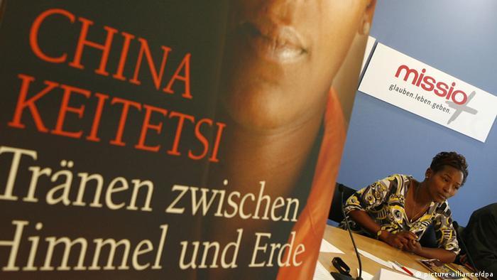 Die Schriftstellerin und ehemalige ugandische Kindersoldatin China Keitetsi stellt in Berlin auf einer Pressekonferenz von UNICEF und Missio ihr neues Buch Tränen zwischen Himmel und Erde vor. Das Buchcover ist vorne links im Bild zu sehen. China Keitetsi selber ist nur ganz klein im Bild unter dem UNICEF-Banner. (Foto: Klaus-Dietmar Gabbert dpa/lbn)