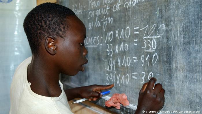 Ein ehemaliger Kindersoldat aus Ostkongo steht an einer Tafel und löst die Rechenaufgabe, die dort angeschrieben ist. (Foto: Wolfgang Langenstrassen)