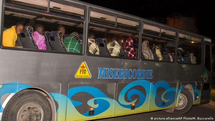 In einem drauen Bus werden die überlebenden Flüchtlinge in ihre Unterkunft auf Lampedusa gebracht. Hinter den Fesntern sitzen nur Mjunge Männer. (Foto: AP Photo/Mauro Buccarello)
