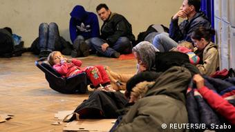 Refugees setting on the floor. (Photo: REUTERS/Bernadett Szabo)