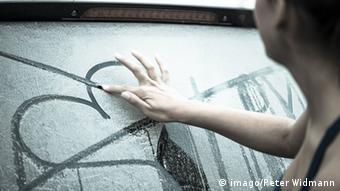 Symbolbild Verzweiflung: Eine Frau schaut traurig auf ein auf den Boden gemaltes Herz mit einem Pfeil