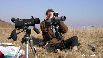 A birdwatcher sitting on a hill with camers and binoculars