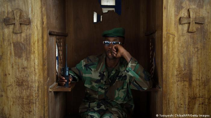 A man in a camouflage uniform and sunglasses listens to a radio