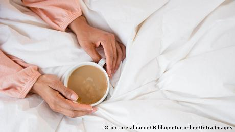 Frau mit Kaffeetasse im Bett