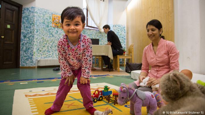 Ein kleines Mädchen blickt in die Kamera, daneben sitzt ihre Mutter (Foto: SJ-Bild/Leopold Stübner SJ)