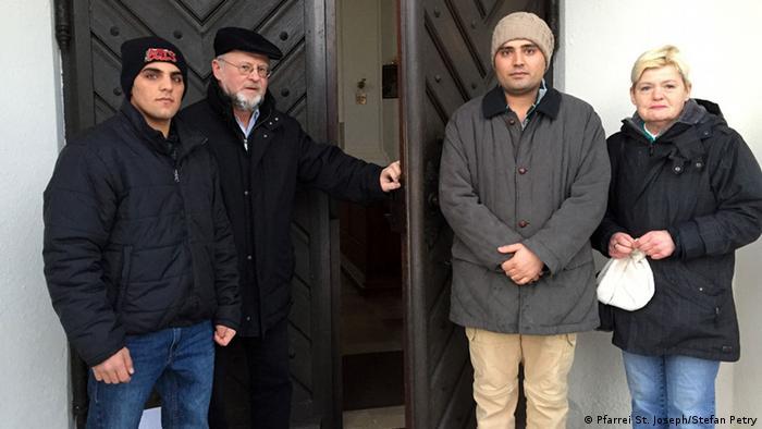 Vor der Kirchentür steht Pfarrer Peter Brummer mit zwei Asylbewerbern aus Afghanistan und der Betreuerin Angelika Pfaffendorf (Foto: Pfarrei St. Joseph/Stefan Petry)