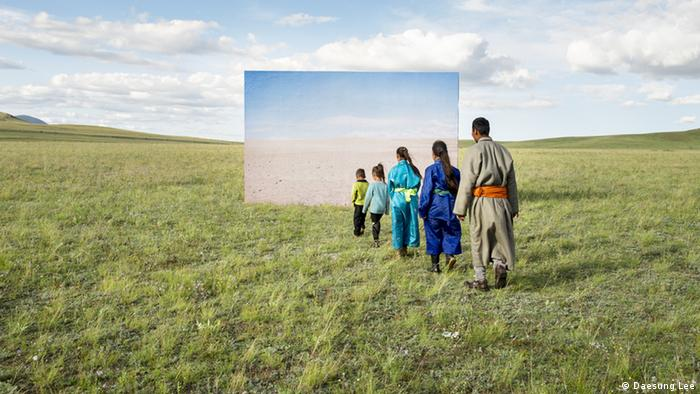 A series of people walk across the grass towards a large canvas of a desert landscape erected on a field
