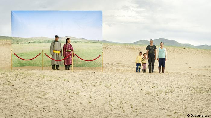An elderly couple depicted on a life-size canvas with green backdrop, look at a young family standing in a sandy landscape