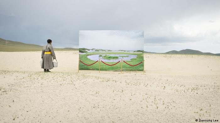 A life-size canvas of a watering hole in a green landscape stands on sand