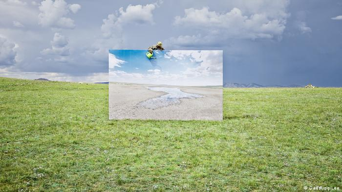 A life-size canvas in a green field. Above it a man is pouring water from a watering can onto it