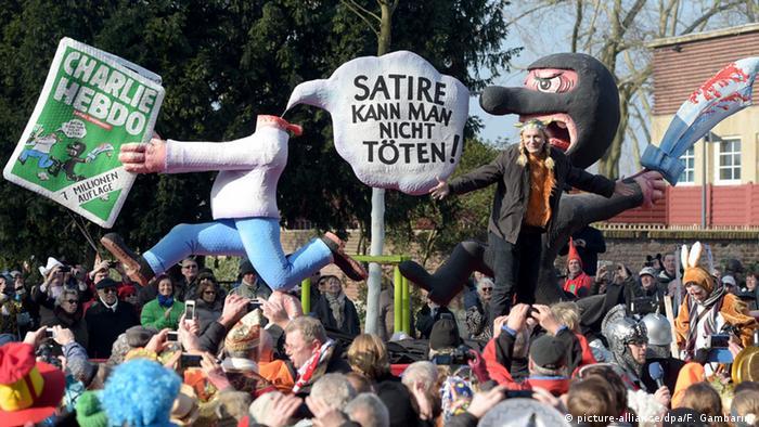 Der Charlie Hebdo Wagen beim Rosenmontagszug in Düsseldorf. Eine Figur mit abgehacktem Kopf hält die Zeitschrift Charlie Hebdo in der Hand, dahinter eine maskierte Figur mit einem Krummsäbel. Karneval 2015 Rosenmontag Charlie Hebdo (picture-alliance/dpa/F. Gambarini)
