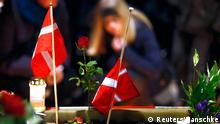 16.2.2015 Danish flags are placed next to flowers as people gather for a memorial service held for those killed on Saturday by a 22-year-old gunman, in Copenhagen February 16, 2015. Danish police said on Monday they had charged two people with aiding the man suspected of shooting dead two people in attacks on a synagogue and an event promoting free speech in Copenhagen at the weekend. The shootings, which Danish Prime Minister Helle Thorning-Schmidt called acts of terrorism, sent shockwaves through Denmark and have been compared to the January attacks in Paris by Islamist militants that killed 17. REUTERS/Hannibal Hanschke (DENMARK - Tags: CRIME LAW POLITICS CIVIL UNREST)