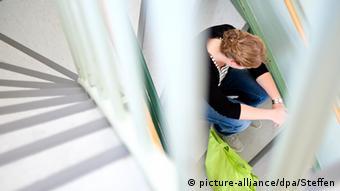 Женщина сидит на лестничной площадке
