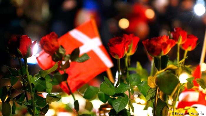 Flowers and a Danish flag are seen during a memorial service held for those killed on Saturday by a 22-year-old gunman, in Copenhagen February 16, 2015.