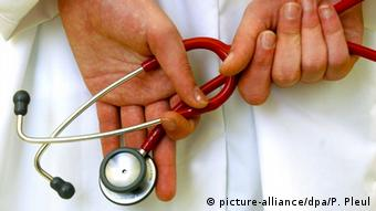 A red stethoscope and a pair of hands
