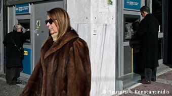 A woman walking away from a Greek ATM machine.