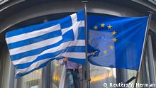 19.02.2015 * A man adjusts a Greek (L) and a European flag outside the Greek embassy in Brussels February 19, 2015. Greece formally requested a six-month extension to its euro zone loan agreement on Thursday, offering major concessions as it raced to avoid running out of cash within weeks, but immediately ran into strong objections from EU paymaster Germany. REUTERS/Yves Herman (BELGIUM - Tags: POLITICS BUSINESS)