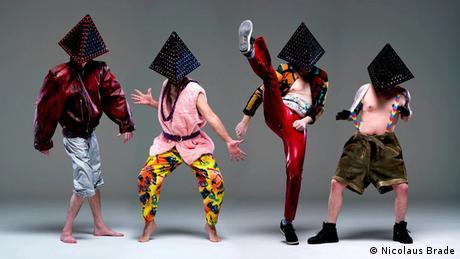 Die vier Mitglieder der deutschen Band Deichkind stehen nebeneinander vor einem grauen Hintergrund.