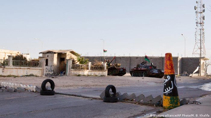 Military tanks are seen outside the broadcast station in Sirte