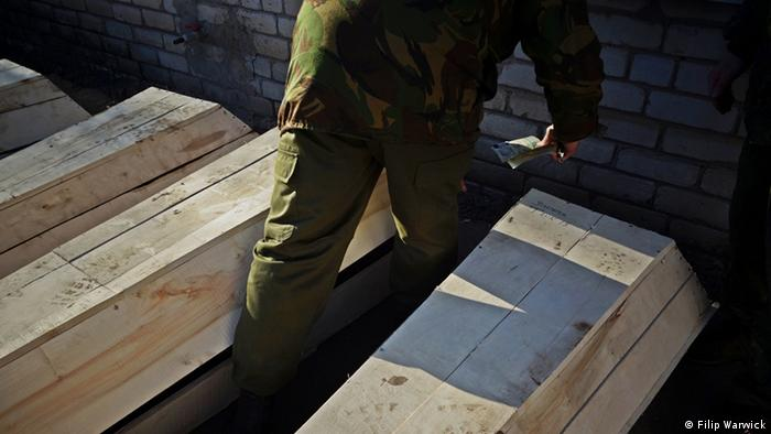 A man walks between wooden coffins
