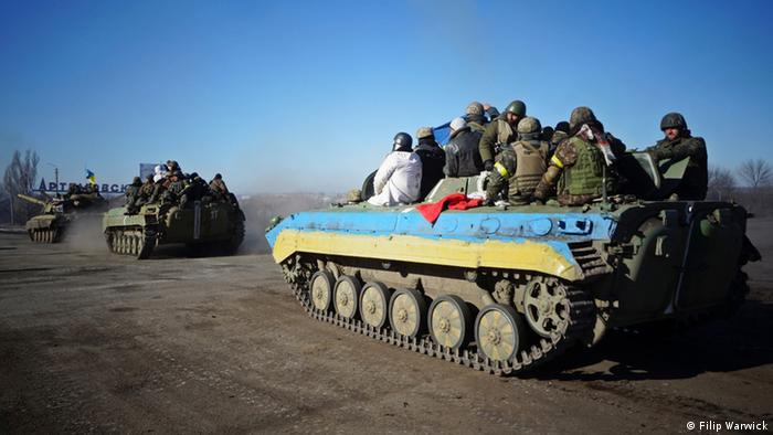 Tanks head down a road toward a sign that reads Artemivsk