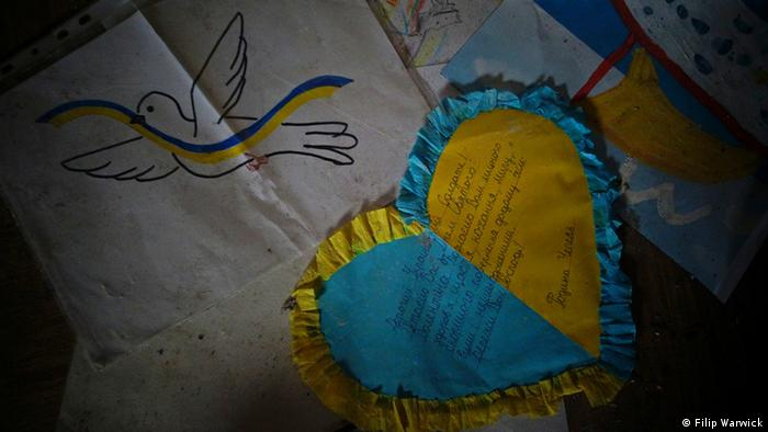 A drawing of a dove and a heart made of yellow and blue paper litter a floor
