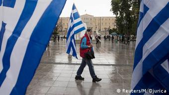 Человек с флагом Греции на фоне парламента страны