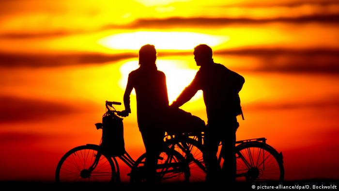 Two cyclists seen against the sun (picture-alliance/dpa/D. Bockwoldt)