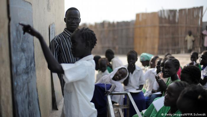 A child writes on a blackboard outside in South Sudan