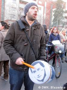 A protester in Skopje bangs a drum - with an image of Gruevski printed on the drum's skin.