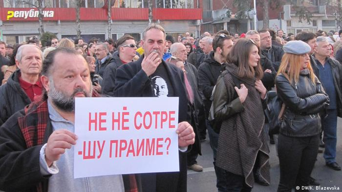 Protesters in Skopje, on February 21, 2015. One, in the foreground, holds a placard.