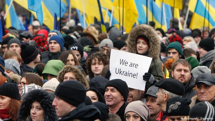 Девочка на плече у взрослого держит плакат на английском языке Мы - Украина во время акции памяти жертв Майдана в Киеве 22 февраля 2015 года