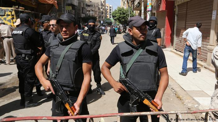 Egyptian policemen stand guard outside a court during the trial of supporters of toppled president Mohamed Morsi