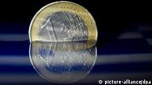 Eine Euro-Münze spiegelt sich am 23.02.2015 in Düsseldorf (Nordrhein-Westfalen im Wasser. Aus Finanzkreisen wurde unterdessen bekannt, dass die Liste mit den Reformvorschlägen der griechischen Regierung noch am 23.02. abgeschickt werden soll. Die Eurogruppe wird dann entscheiden, ob die Athener Vorschläge ausreichend sind, um Griechenland weitere Finanzhilfen zu gewähren.Foto: Federico Gambarini/dpa +++(c) dpa - Bildfunk+++