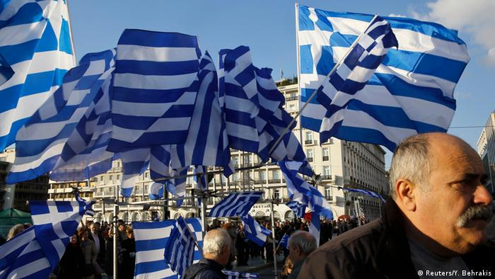 Greek national flags displayed for sale flutter during an anti-austerity pro-government demonstration in front of the parliament in Athens February 15, 2015.