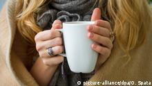 ILLUSTRATION - Eine Frau wärmt sich am 20.10.2014 in Hannover (Niedersachsen), in eine Decke gehüllt, an einer Tasse Tee. Foto: Ole Spata/dpa (zu dpa: Die Heizung macht wärmer, ärmer - und sorgt manchmal für Streit vom 21.10.2014)