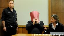 Niels Höger covers face in court