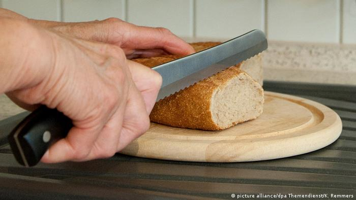 Someone cutting a loaf of bread