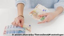 ILLUSTRATION - Eine junge Frau zaehlt am 04.11.2014 in einem Studio in Berlin Geldscheine auf den Tisch.