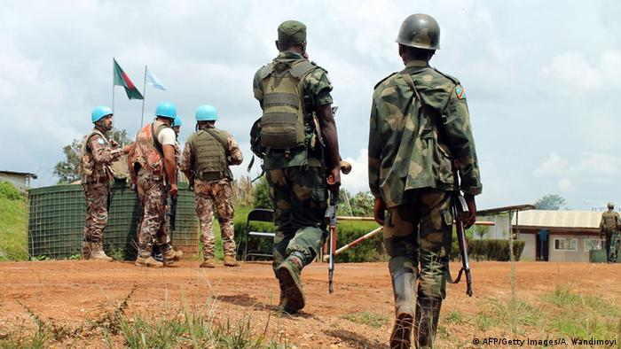 Congo soldier walk past UN peacekeepers (AFP/Getty Images/A. Wandimoyi)