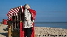 aeltere Frau lehnt an einem Strandkorb und geniesst die Sonne, Deutschland, Mecklenburg-Vorpommern, Gollwitz | elderly woman leaning against a beach chair and enjoy the sun, Germany, Mecklenburg-Western Pomerania, Gollwitz